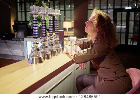 Young curly woman sits at bar counter in evening cafe.