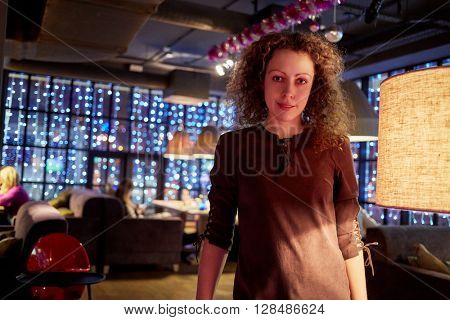 Young curly woman stands in evening cafe near floor-lamp.