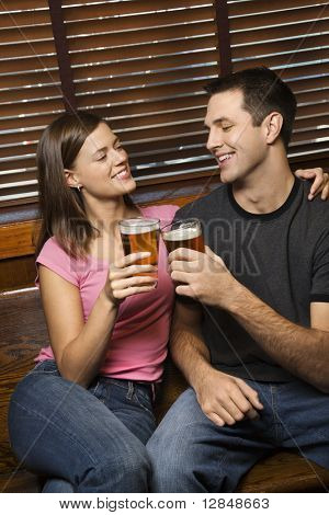 Young man and woman sitting together toasting their beers while relaxing at a pub. Vertical shot.