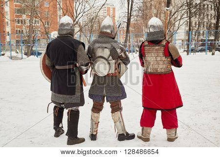 Three men dressed in defensive knight costumes stand in courtyard in winter.