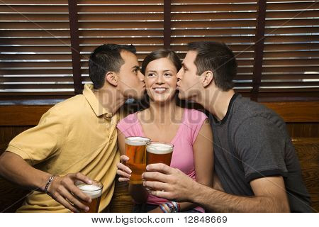 Two young men kissing a females cheek while holding their beers at a pub. Horizontal shot.