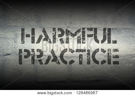 harmful practice stencil print on the grunge white brick wall