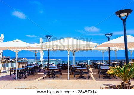 Cozy cafe on the shore of warm sea. Above the tables snow-white tents are opened