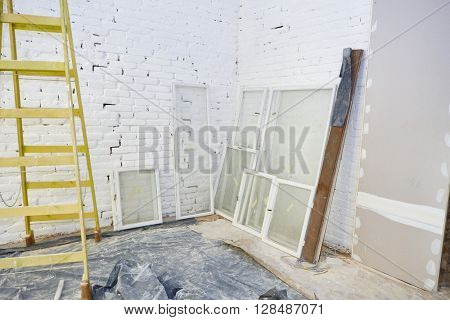 Apartment under construction with ladder and window frames supported by wall.