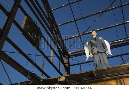 Young businessman with serious expression wears angel wings and stands in an abandoned building. Horizontal shot.