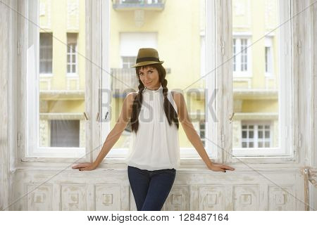 Pretty casual woman standing at window, wearing hat, looking at camera.