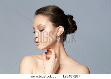 beauty, jewelry, accessories, people and luxury concept - close up of beautiful asian woman face with earring over gray background