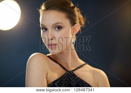 beauty, jewelry, people and luxury concept - face of beautiful young asian woman with earring over black background and spotlights