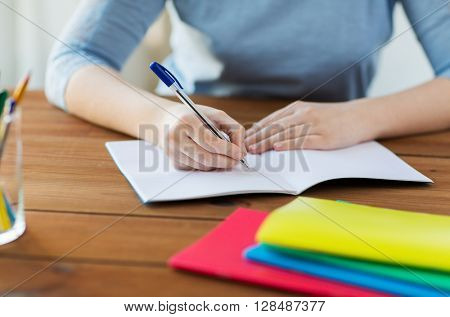 high school, education, people and learning concept - close up of student or woman writing to notebook at home