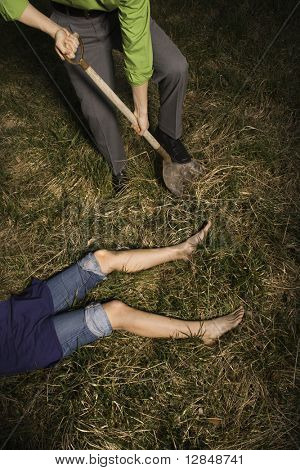 Businessman digs into the ground with a shovel to bury a womans body. Vertical shot.