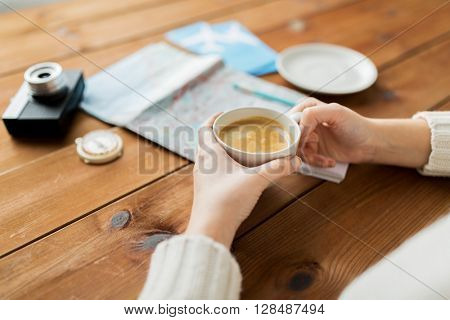 vacation, tourism, travel, destination and people concept - close up of hands with coffee cup and travel stuff