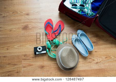 summer vacation, travel, tourism and objects concept - close up of travel bag with clothes and stuff