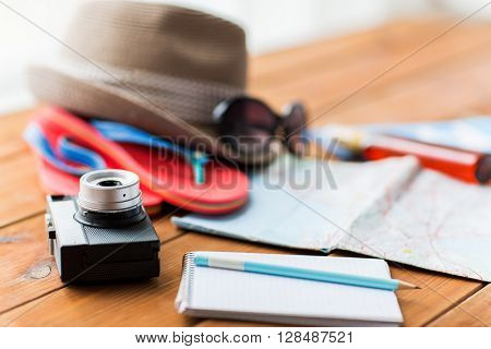summer vacation, travel, tourism and objects concept - close up of camera, notepad with pencil and personal accessories