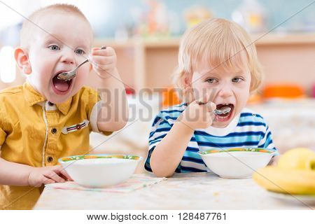 Funny little kids eating from plates in kindergarten