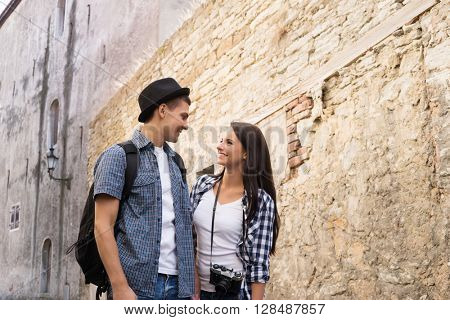 Beautiful, smiling couple having a pleasant walk in old town.