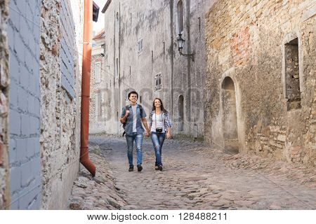 Young traveling couple having a medieval walk on an old street with tile road.