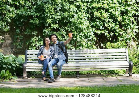 Beautiful young couple sitting on the bench with a cup of coffee in summer time.