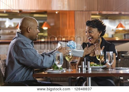 African-American man giving a surprised woman a gift-wrapped present at a restaurant. Horizontal shot.