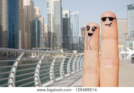family, couple, travel, tourism and body parts concept - close up of two fingers with smiley faces over dubai city street or waterfront background