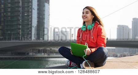 technology, travel, tourism, music and people concept - smiling young woman or teenage girl with tablet pc computer and headphones over dubai city street background