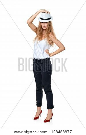 Beautiful slytish woman in full length posing in fedora hat, over white background