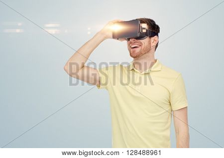 3d technology, virtual reality, entertainment and people concept - happy young man with virtual reality headset or 3d glasses over gray background