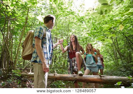 adventure, travel, tourism, hike and people concept - group of smiling friends walking with backpacks and climbing over fallen tree trunk in woods