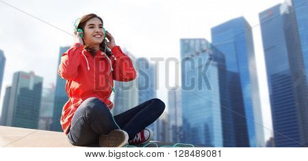 technology, travel, tourism and people concept - smiling young woman or teenage girl in headphones listening to music over singapore city skyscrapers background