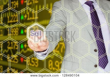 Businessman in a grey suit pressing the sell button an a hexagon grid in front of a stock ticker wall