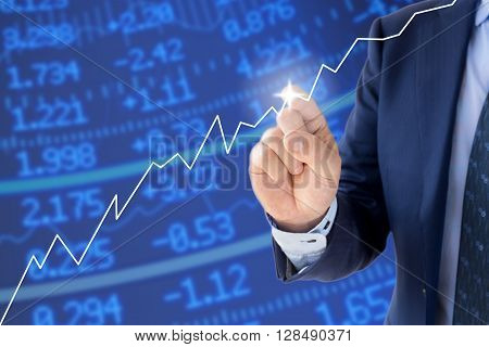 Businessman in a blue suit pointing at a rising chart in front of a stock wall