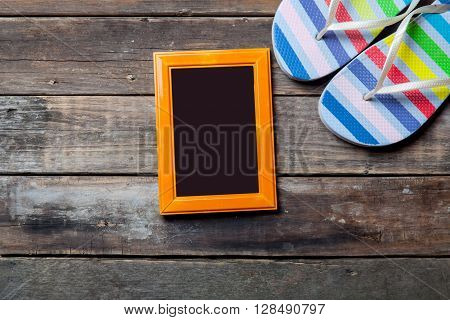 photo frame and colorful sandals on the brown wooden background
