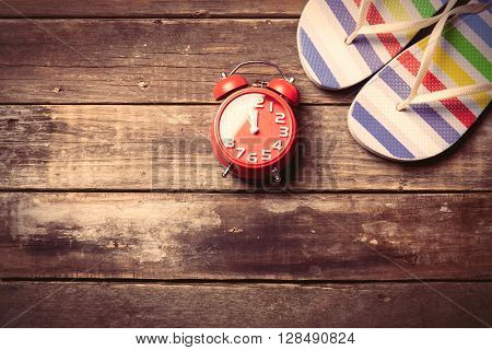 photo of the red clock and colorful sandals on the brown wooden background