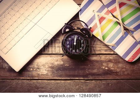 photo of the black clock laptop and colorful sandals on the brown wooden background