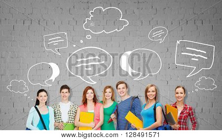 education, school and people concept - group of smiling teenage students with folders and school bags over gray brick wall background with text bubbles