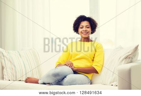 people, race, ethnicity and leisure concept - happy african american young woman sitting on sofa at home
