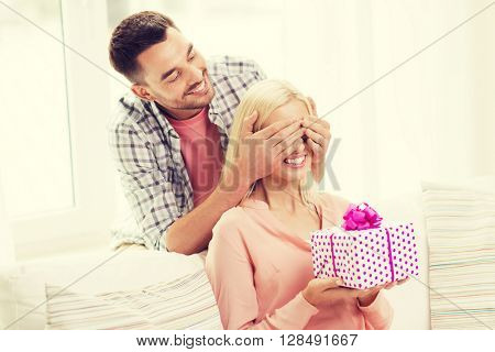 relationships, love, people, birthday and holidays concept - happy man covering womans eyes and giving gift box at home