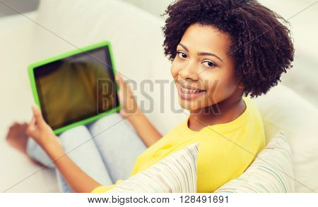 people, technology, advertisement and leisure concept - happy african american young woman sitting on sofa and showing tablet pc computer black blank screen at home