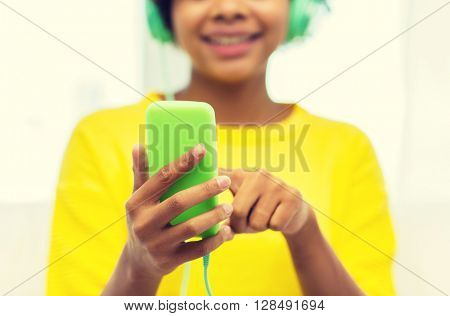 people, technology and leisure concept - close up of happy african american young woman sitting on sofa with smartphone and headphones listening to music at home