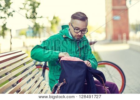 people, style, leisure and lifestyle - young hipster man with backpack sitting on city bench