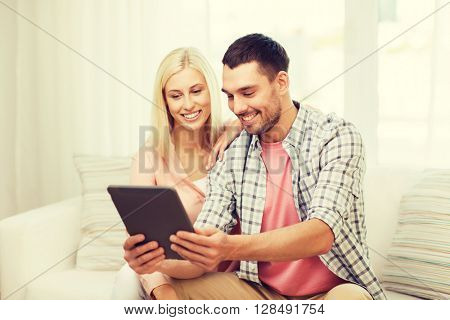 love, family, technology, internet and happiness concept - smiling happy couple with tablet pc computer at home