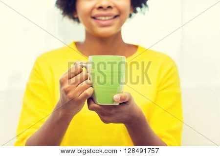 people, drinks and leisure concept - close up of happy african american woman drinking tea from cup or mug at home