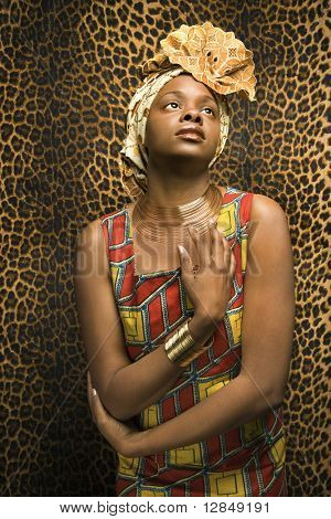 Portrait of an African American woman wearing traditional African clothing in front of a patterned wall. Vertical format.