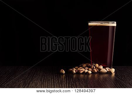 The beer red ale and snacks. The dark background.