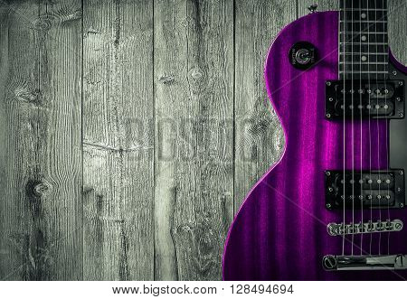 Part of the pink electric guitar on wooden background. A place for writing of the text