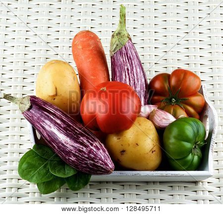 Arrangement of Fresh Raw Vegetables with Striped Eggplants Green and Red Tomatoes Potato Carrot and Garlic on Wooden Tray closeup on Wicker background