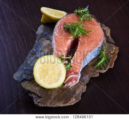 Perfect Raw Salmon Steak with Slices of Lemon and Rosemary on Shale Stone Board closeup on Dark Wooden background