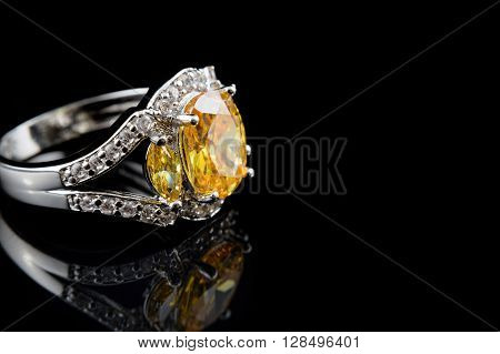 Silver or white gold ring with yellow gems and diamonds on black glass background