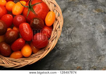 Top view of a basket filled with a variety of medley tomatoes. Horizontal format with copy space.