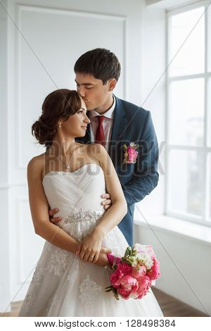 Wedding couple in love. Beautiful bride in white dress with brides bouquet and handsome groom in blue suite standing and embracing indoors in decorated studio room, white bright interior with big window. Husband kissing his wife