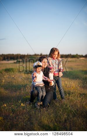 mother with children on a meadow near the forest